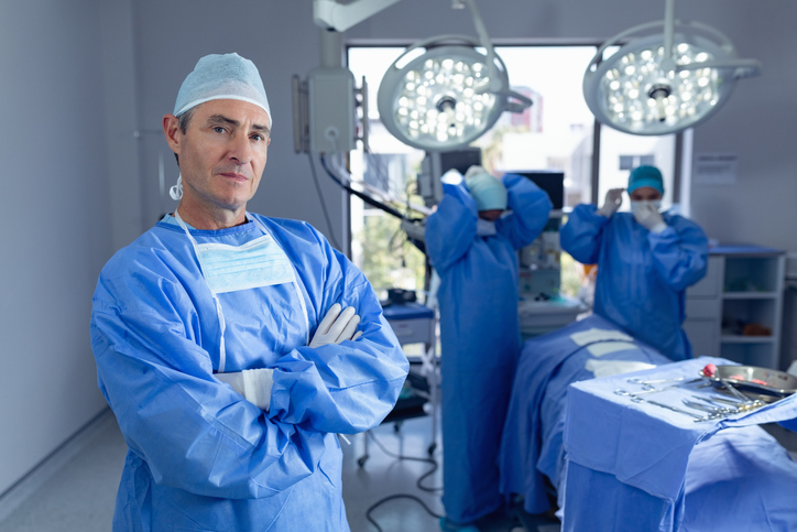 Portrait of Caucasian male surgeon standing with arm crossed while diverse surgeons performing surgery in operation room while surgeons getting ready for operation at hospital